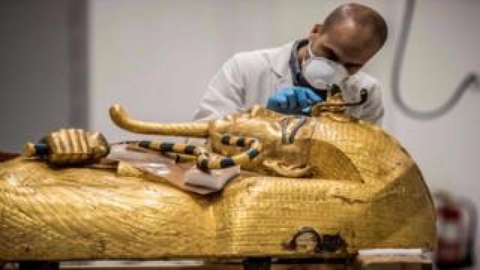 An Egyptian archeologist performs restorations on the golden sarcophagus of the ancient Egyptian Pharaoh Tutankhamun