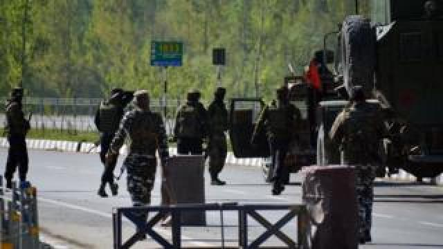 Indian army soldiers enforce restrictions on the national highway as military convoy passes on the outskirts of Srinagar, Kashmir on April 10, 2019