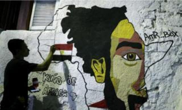On Monday, a man is seen daubing paint onto a mural which depicts Mo Salah, the outline of the African Continent, and the Egyptian flag.