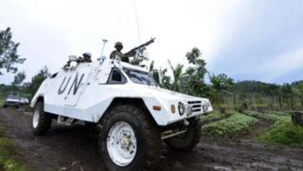 UN peacekeepers in Congo drive in armoured vehicle.
