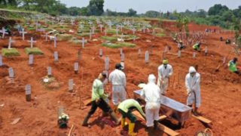 A coronavirus victim is buried in a graveyard in Jakarta, Indonesia.