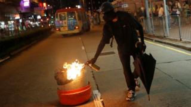 A demonstrator sets a bin on fire in Hong Kong