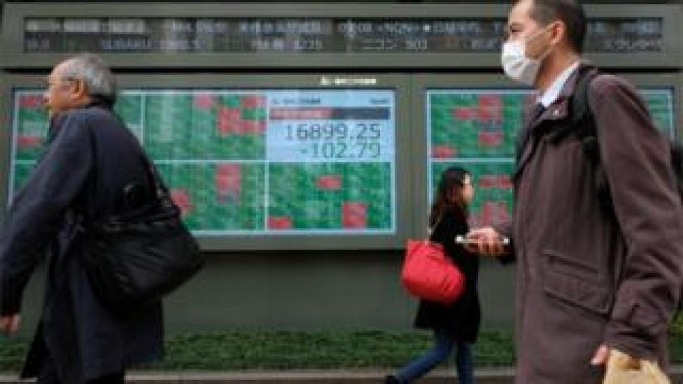 Pedestrians walk past a quotation board displaying share price numbers of the Tokyo Stock Exchange in Tokyo (March 17, 2020).