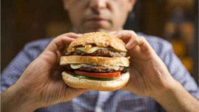 Person holding a burger