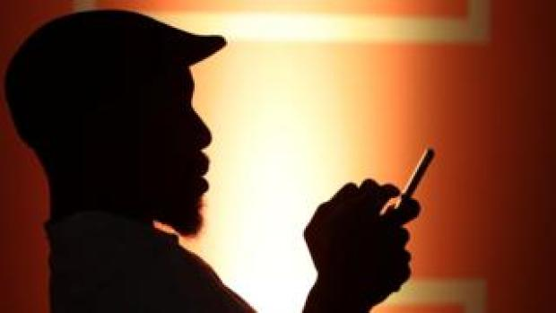 A silhouetted man types on his phone in low light conditions