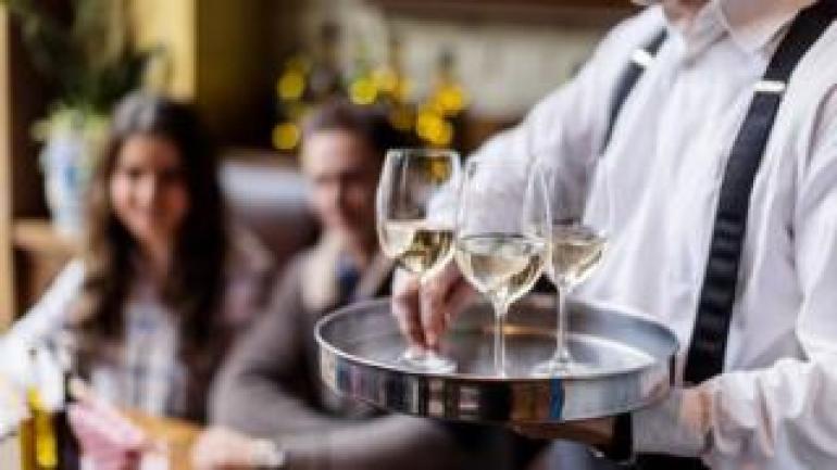 Ein Kellner, der Gläser Wein dient