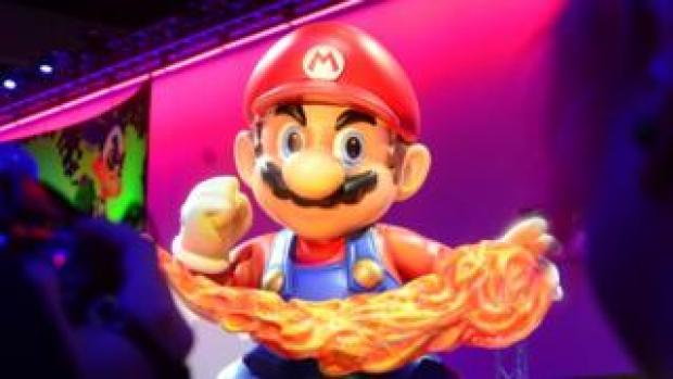 A large figure of Mario wielding a fireball in front of a stage
