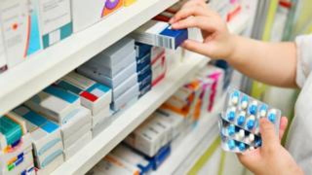 Pharmacist taking drugs from shelves