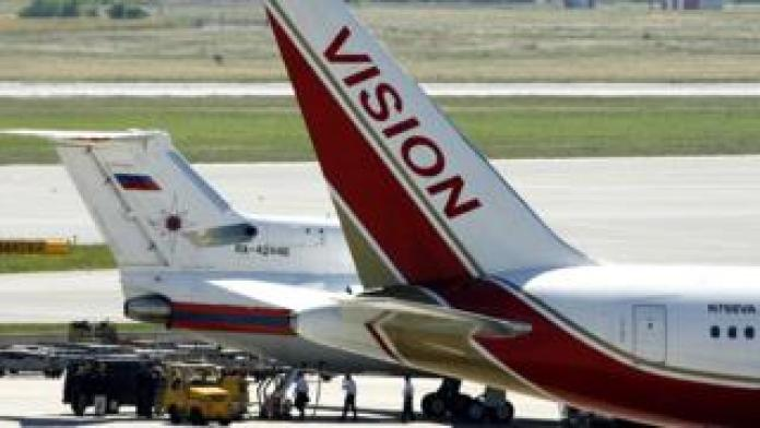 Unidentified officials stand by a Russian emergency situations ministry plane that sits next to a Vision airlines plane presumed to be carrying 10 men and women who worked as Russian spies in the United States at Vienna airport on July 9, 2010 in Vienna