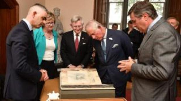 Prince Charles inspects the Great Book of Ireland at University College Cork