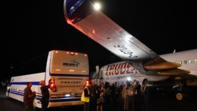 Members of the media and others inspect the damage on the plane's wing.