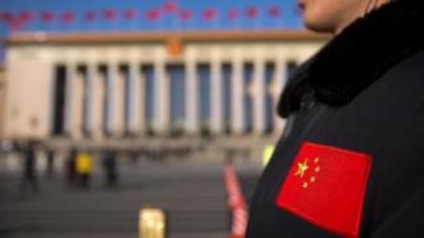 A security official with a Chinese flag patch on his jacket stands guard outside of the Great Hall of the People on 12 March