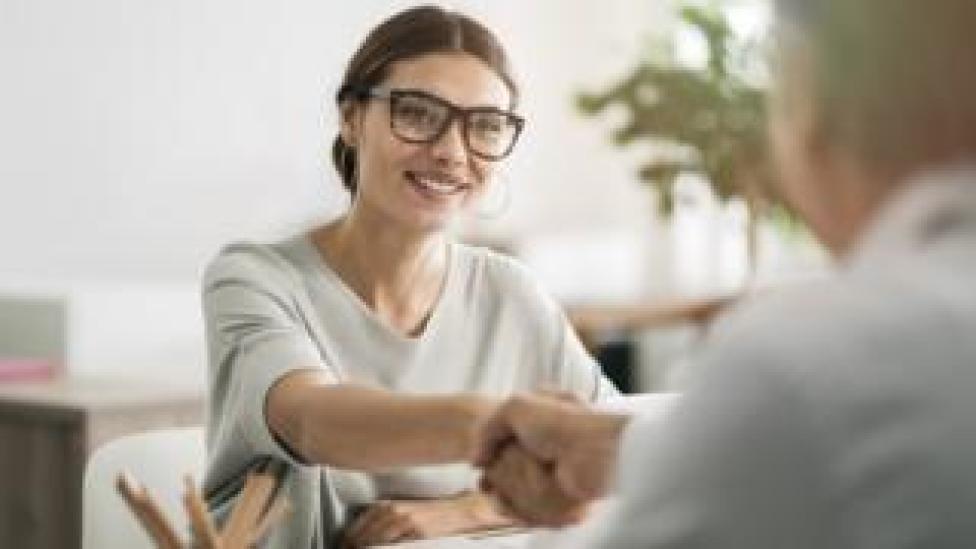 امراة مبتسمة في مقابلة شخصية للحصول على وظيفة