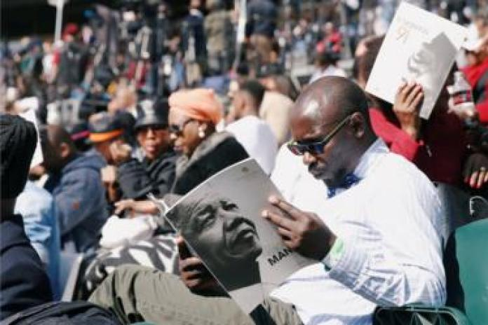 A man holds a program as crowds gather to hear former U.S. President Barack Obama delivering the 16th Nelson Mandela annual lecture, marking the centenary of the anti-apartheid leader's birth, in Johannesburg, South Africa July 17, 2018.