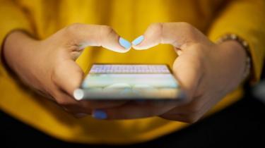 Mãos da mulher segurando um smartphone - ela está vestindo um top amarelo e está tocando na tela do telefone