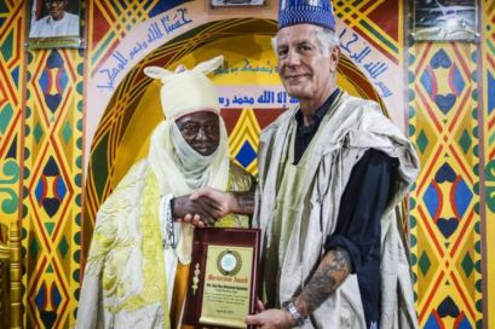 Bourdain accepts an award during a visit to Nigeria.