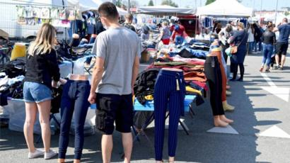 Shoppers check merchandise on sale as a market reopens for trade, in Rzeszow, south east Poland, 10 May 2020
