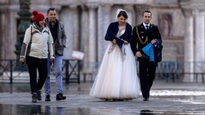 Un couple de jeunes mariés traverse une place inondée à Venise, 14 novembre 2019