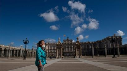 A woman walks in front of the Royal Palace in Madrid on May 10, 2020 during the hours allowed by the government to exercise