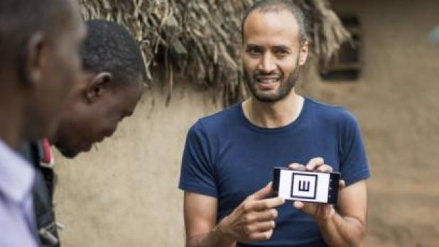 Dr Andrew Bastawrous demonstrates the Peek Acuity app to villagers in Kenya