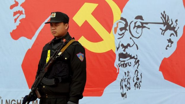 An armed policeman stands guard next to a portrait of late president Ho Chi Minh (R), founder of today's communist Vietnam, and Russian communist leader Vladimir Lenin (L), outside the venue of the current 11th national congress of the Vietnam Communist Party (VCP) in Hanoi on January 17, 2011.