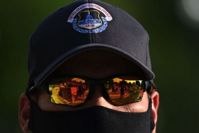 Demonstrators reflections are seen in the glasses of a US Capitol police officer during a protest in front of the United States Capitol in Washington, DC, on June 2, 2020.