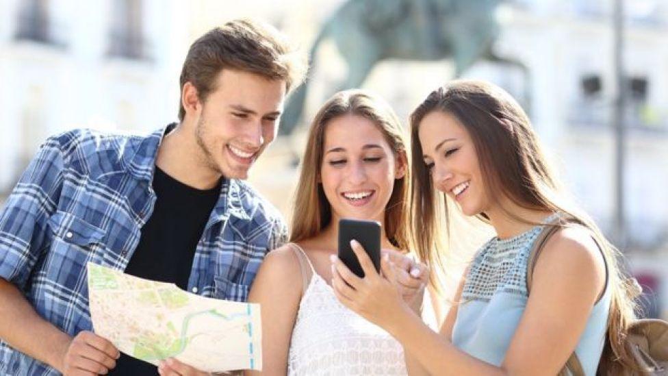 Grupo de 3 jóvenes con mapa y celular