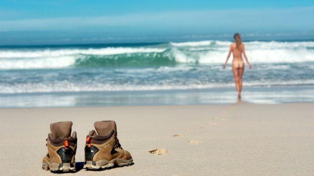 Zapatos dejados en la playa en primer plano y en la distancia chicha desnuda