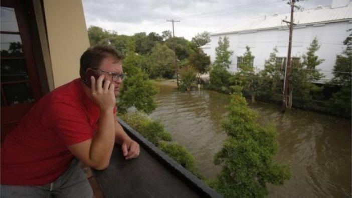 Un hombre habla por teléfono mientras observa la calle inundada