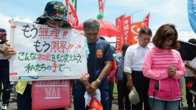 People offer a silent prayer in front of the US Kadena Air Base in Cyatan, Okinawa prefecture, 21 May