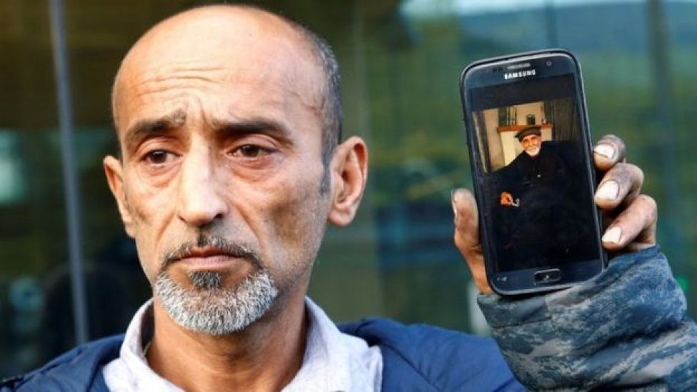 Omar Nabi holds a phone with a picture of his father Daoud, who died in the Christchurch mosque shootings (16 March)