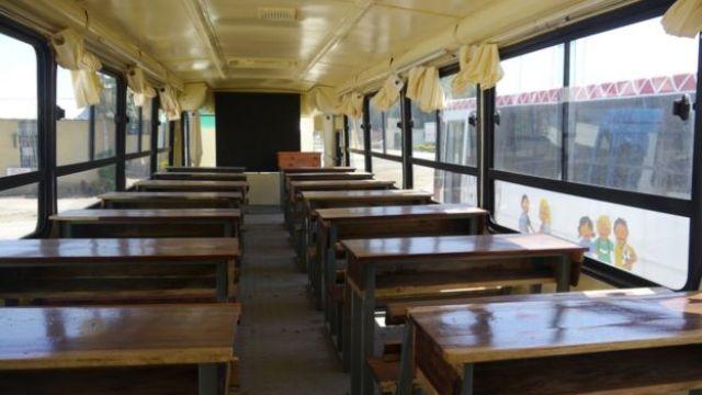 Interior de uma sala-ônibus, ônibus reformado para ser sala de aula; ao fundo um quadro-negro, à frente, carteiras