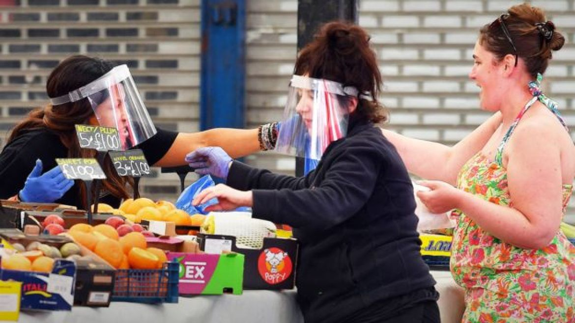 Face masks and gloves worn by two women on a market stall