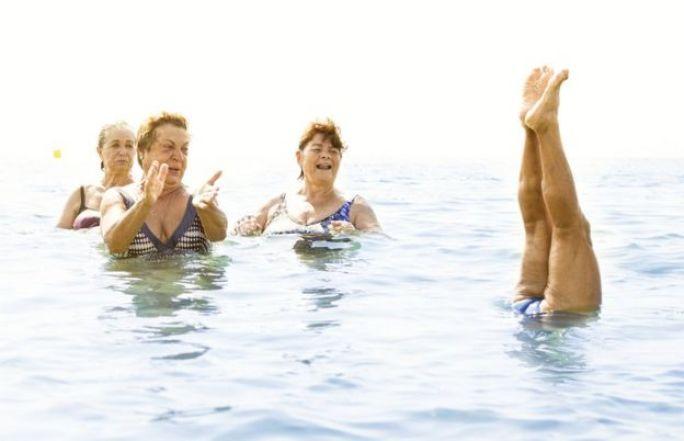 Un grupo de mujeres se divierten en el agua. Una se para de manos.