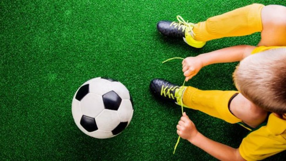 Boy and football on artificial turf