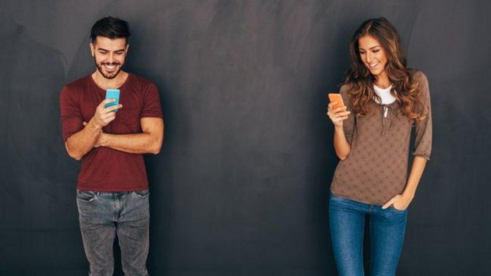 Una pareja de jóvenes con el celular.