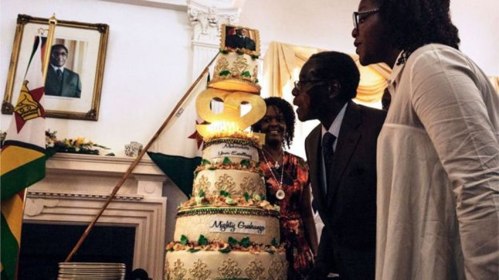 Zimbabwe President Robert Mugabe (C), flanked by his wife Grace Mugabe (L) and daughter Bona (R), blows candles on his cake during a suprise party hosted by the office of the President and Cabinet at State House in Harare, on February 22, 2016 to celebrate his 92nd birthday.