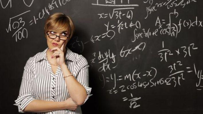Mujer frente a una pizarra con ecuaciones.
