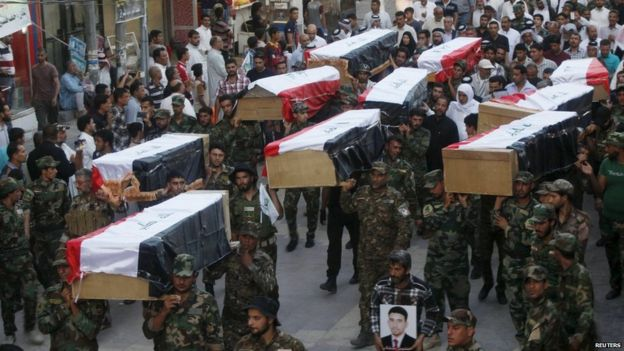 Iraqi Shia militiamen carry the coffins of soldiers killed in the Speicher massacre (1 July 2015