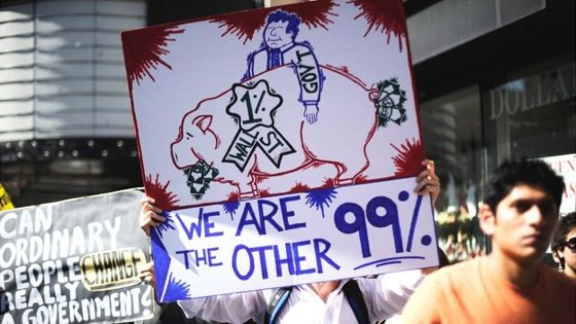 Marcha del movimiento Occupy Wall Street con un cartel que dice:
