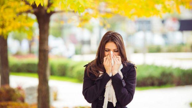 Mujer estornuda.