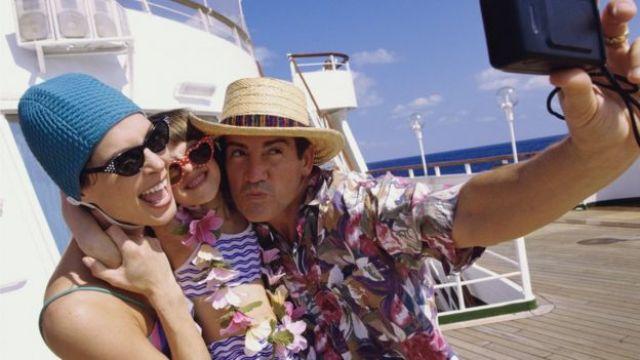 Pai, mãe e filha tiram uma foto a bordo de um cruzeiro