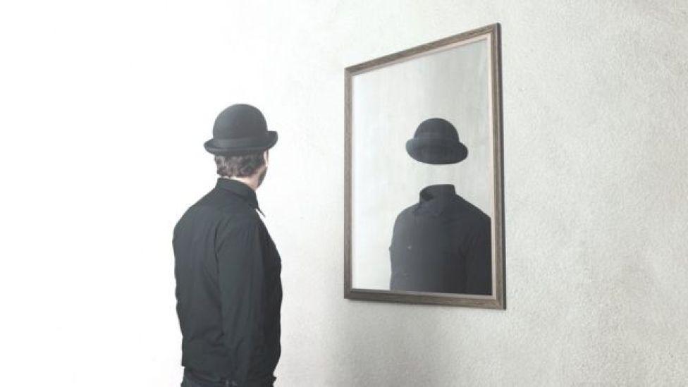 Hombre frente a un espejo en el que no se ve su rostro.