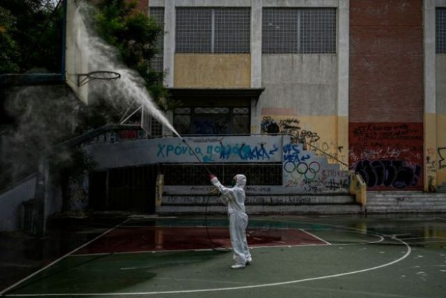 A municipality worker disinfects a high-school yard in Athens