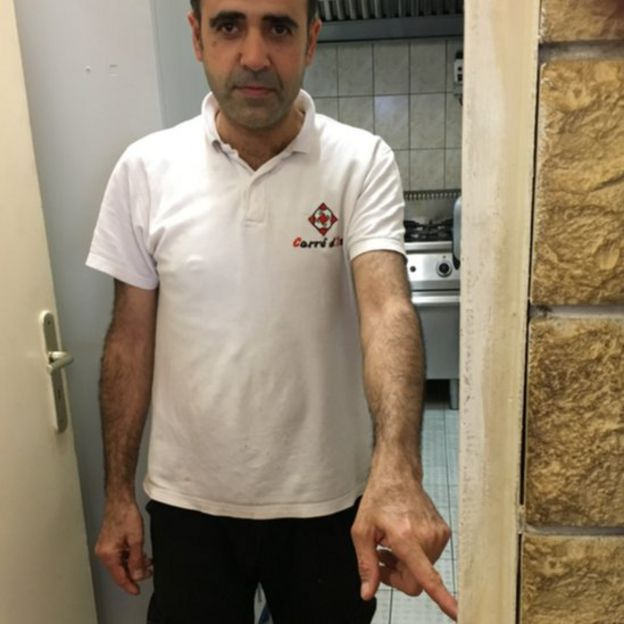 Abdullah points to a bullet hole inside his shop