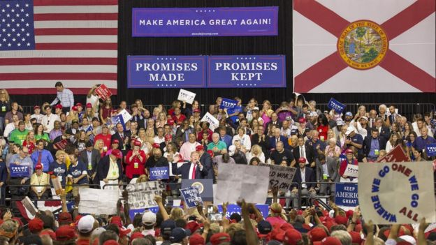 As President Trump speaks at a rally in Florida on 31 July, a QAnon poster is visible (bottom right)