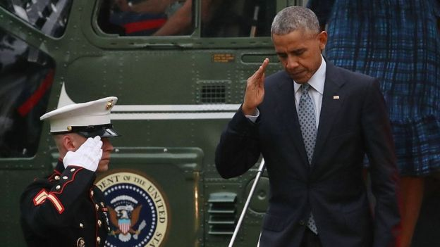 President Barack Obama salutes a US Marine as he steps off Marine One