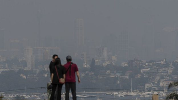 Tourists take in a hazy view of Sydney's skyline amid intense bushfires north of the city