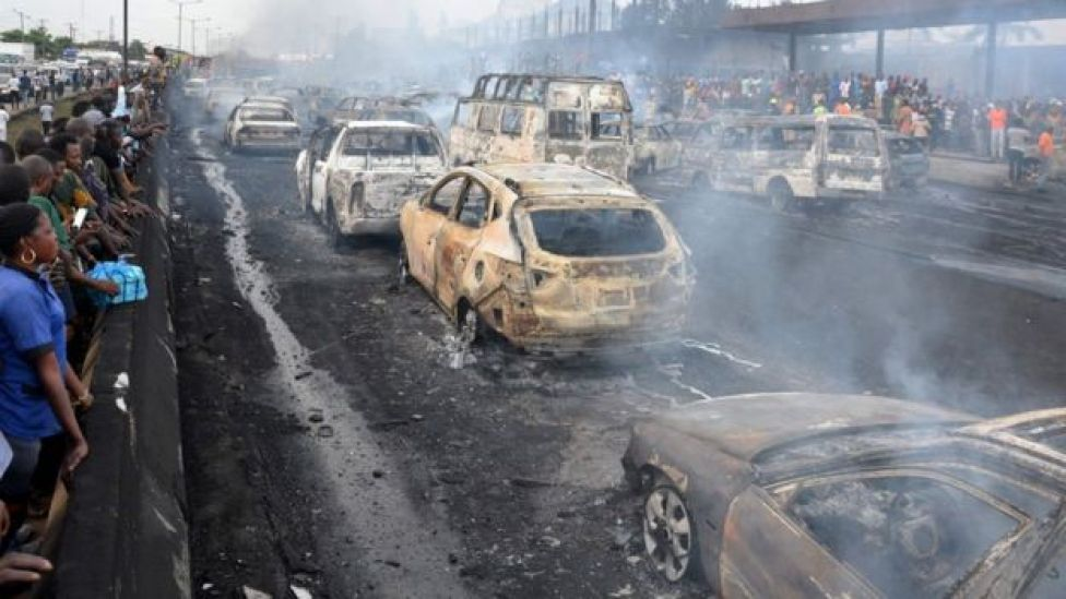 Bystanders and emergency service rescuers observe at the scene of an oil tanker explosion on a highway in Lagos, 28 June 2018