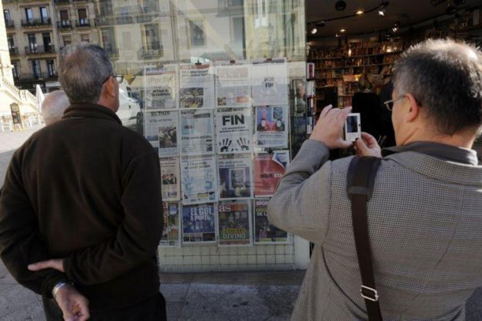 Un hombre fotografía con la cámara de su celular las portadas de varios diarios en San Sebastián el 21 de octubre de 2011, después de que ETA anunciara el